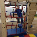 Photo of toddler climbing on an indoor play structure