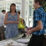 Photo of teenage boy explaining project to a woman viewer at exhibit table