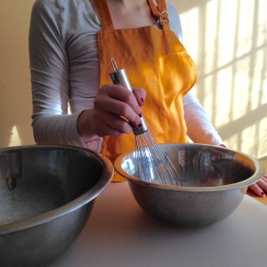 photo of teenage girl in apron with whisk and mixing bowl