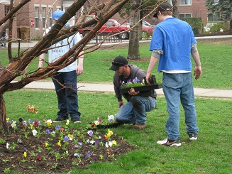 Keene State College landscaper on his knees planting flowers, 2 teenage boys standing next to him