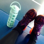 Photo of feet in gym shoes next to water bottle
