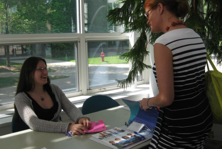 Photo of high school age girl at exhibit table smiling at guest
